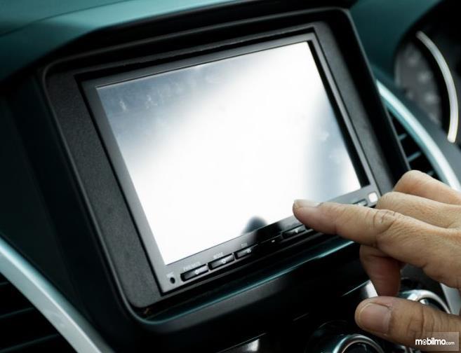 Gambar ini menunjukkan sebuah jari menunjuk head unit mobil