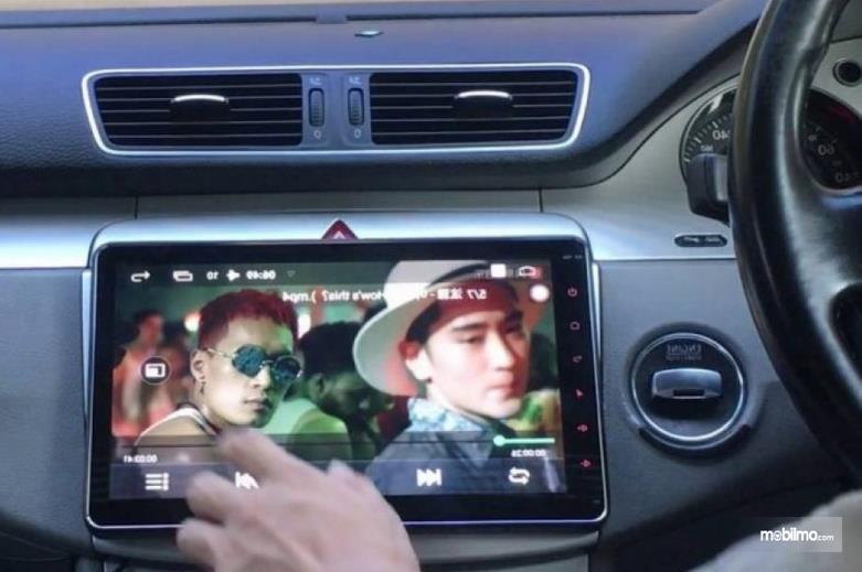Gambar ini menunjukkan sebuah tangan menhgoperasikan head unit mobil