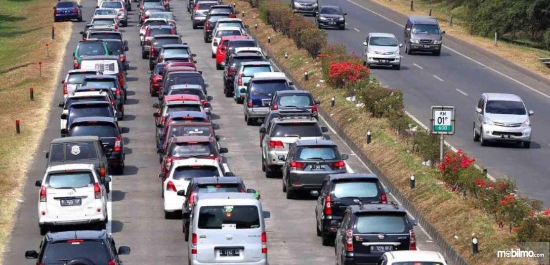 Gambar ini menunjukkan banyak mobil melaju di jalanan