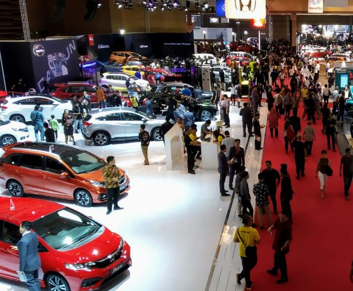 Gambar ini  menunjukkan banyak orang di pameran mobil