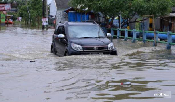 Gambar ini menunjukkan mobil hitam menerjang banjir cukup dalam