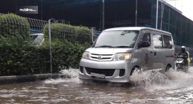 Gambar ini menunjukkan mobil melaju saat jalanan banjir