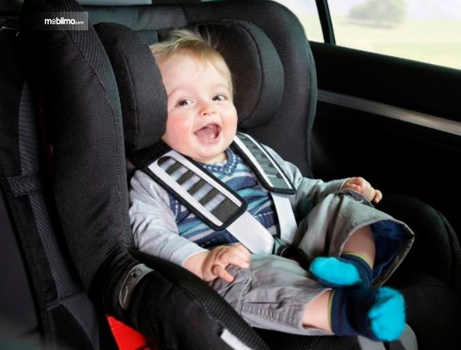 Gambar ini menunjukkan anak-anak duduk di Child Seat Mobil