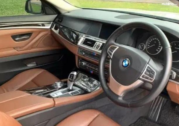 Gambar ini menunjukkan dashboard dan kemudi mobil Mobil BMW 520i 2011