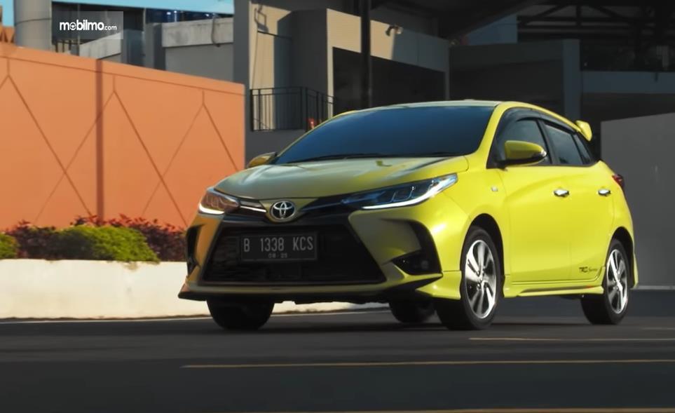 Gambar ini menunjukkan mobil Toyota Yaris kuning tampak depan