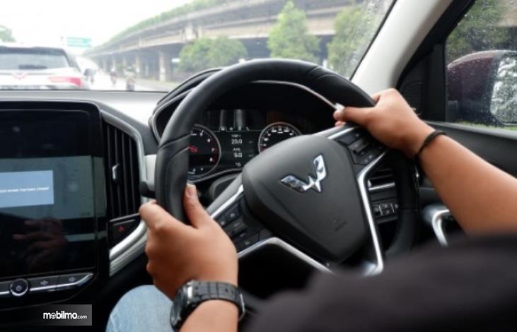 gambar ini menunjukkan 2 tangan memegang kemudi mobil Wuling