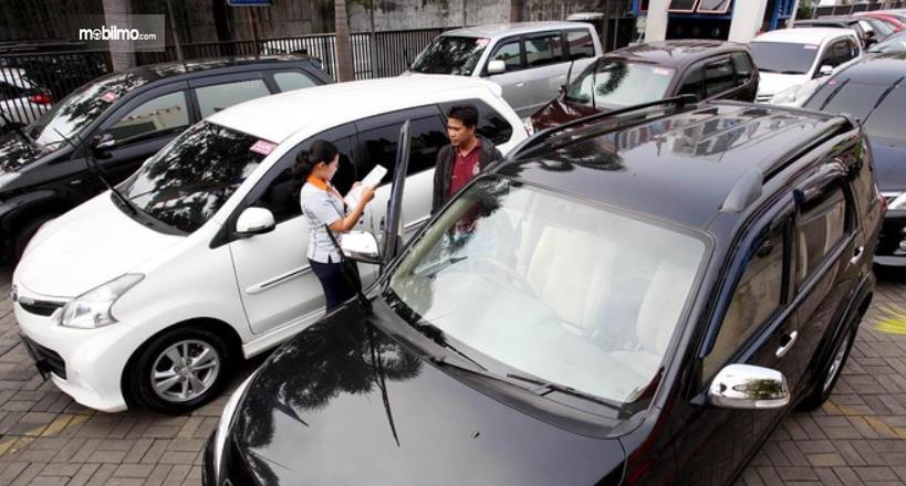 Gambar ini menunjukkan 2 orang dan beberapa mobil