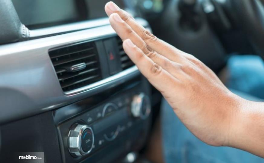 Gambar ini menunjukkan sebuah tangan didekatkan pada kisi-kisi AC mobil