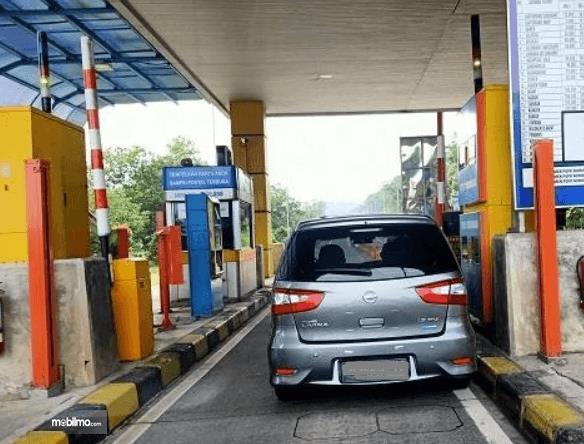 Gambar ini menunjukkan sebuah mobil berada di gerbang tol