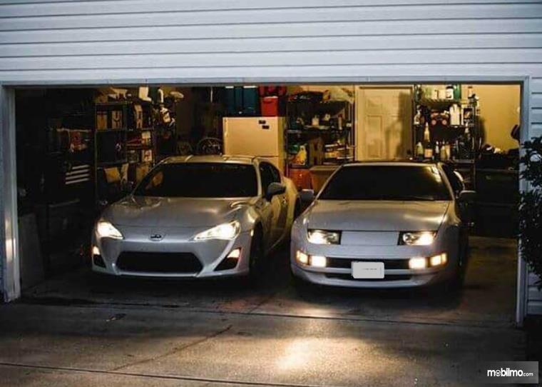 Gambar ini menunjukkan 2 mobil di garasi rumah