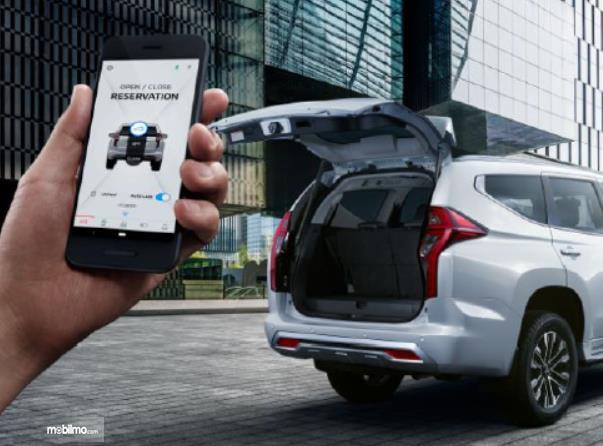 Gambar ini menunjukkan pengoperasian smartphone untuk membuka pintu belakang mobil