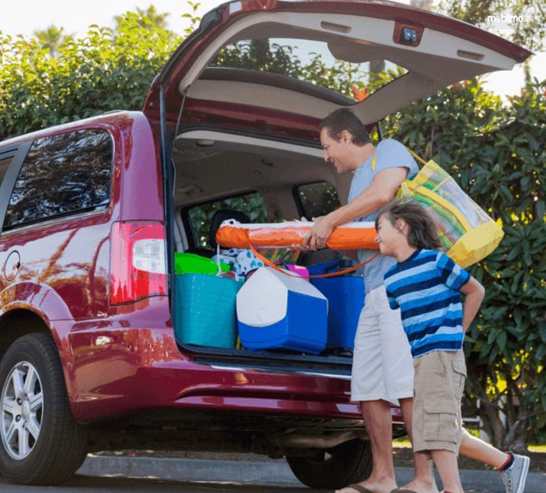 Gambar iini menunjukkan seorang pria dan anaknya mengisi bagasi mobil dengan barang bawaan