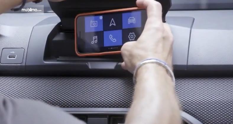 Gambar ini menunjukkan pemasangan Smartphone untuk sistem infotainment pada kendaraan