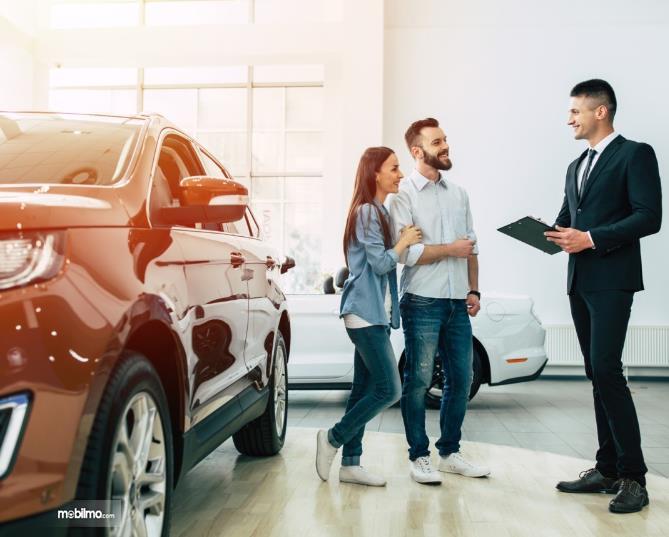 Gambar ini menunjukkan beberapa orang sedang melakukan pembelian mobil