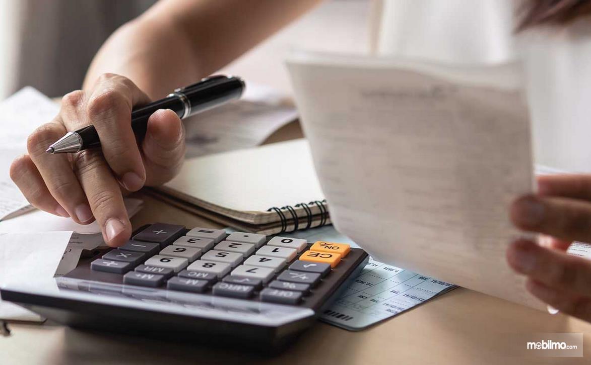 Gambar ini menunjukkan sebuah tangan memegang kalkulator