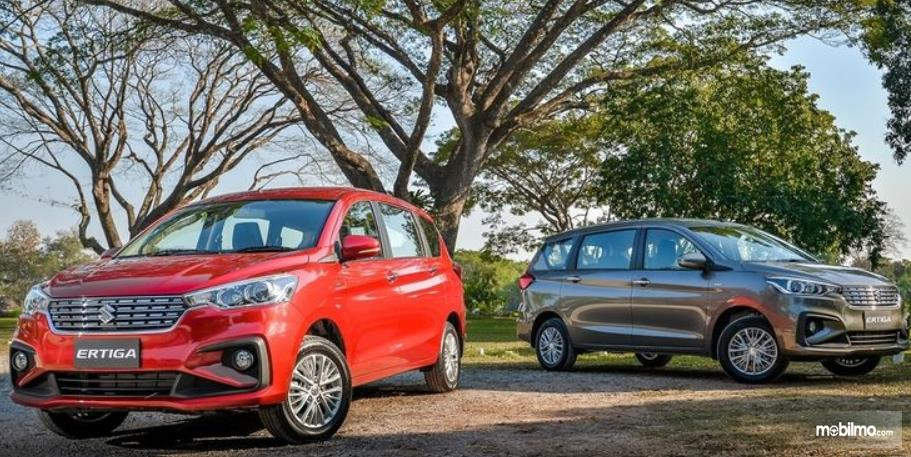 Gambar ini menunjukkan 2 buah mobil dengan warna merah dan abu-abu