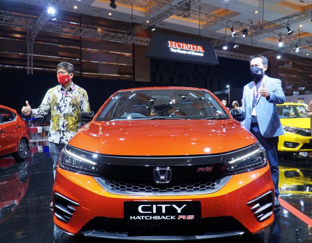 Gambar ini menunjukkan mobil Honda City Hatchback RS tampak depan dan 2 orang berdiri di sampingnya