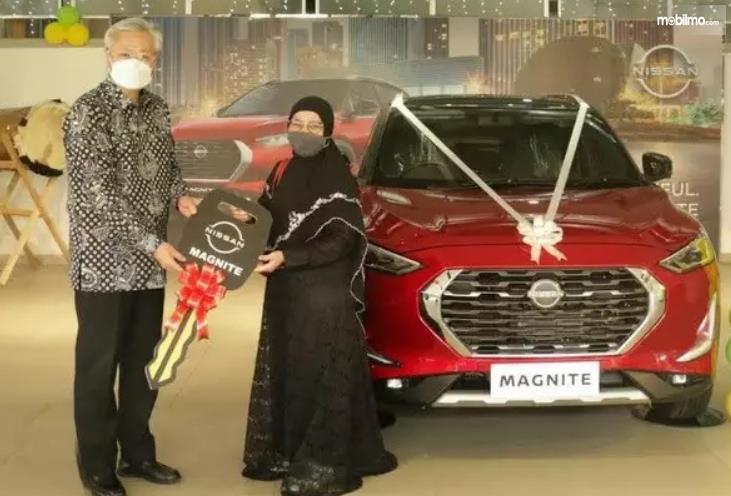 Gambar ini menunjukkan penyerahan mobil pada konsumen pertama Nissan Magnite