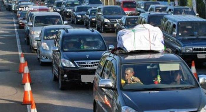 Gambar ini menunjukkan mobil di jalanan dalam kondisi macet