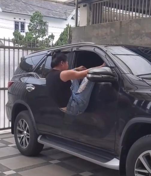 Gambar ini menunjukkan seorang wanita masuk mobil melalui jendela