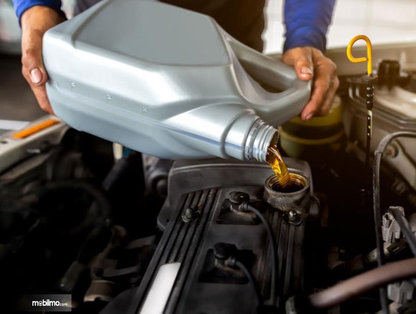 Gambar ini menunjukkan penggantian oli mesin mobil