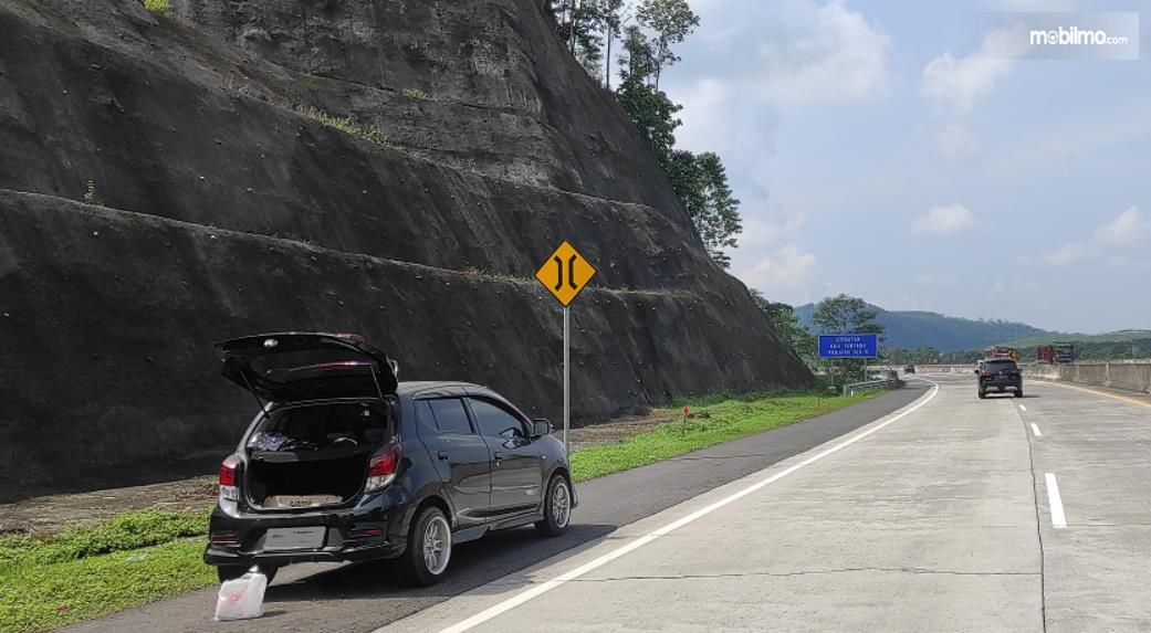 Gambar ini menunjukkan mobil berhenti di pinggir jalan tol dengan pintu belakang terbuka