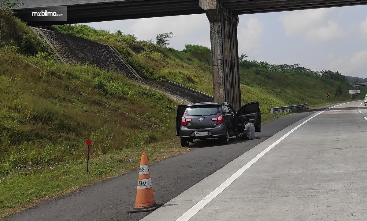 Gambar ini menunjukkan sebuah mobil berhenti di bahu jalan tol dengan segitiga darurat di belakangnya