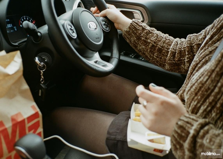 Gambar ini menunjukkan pengemudi sedang memegang kemudi dan makanan