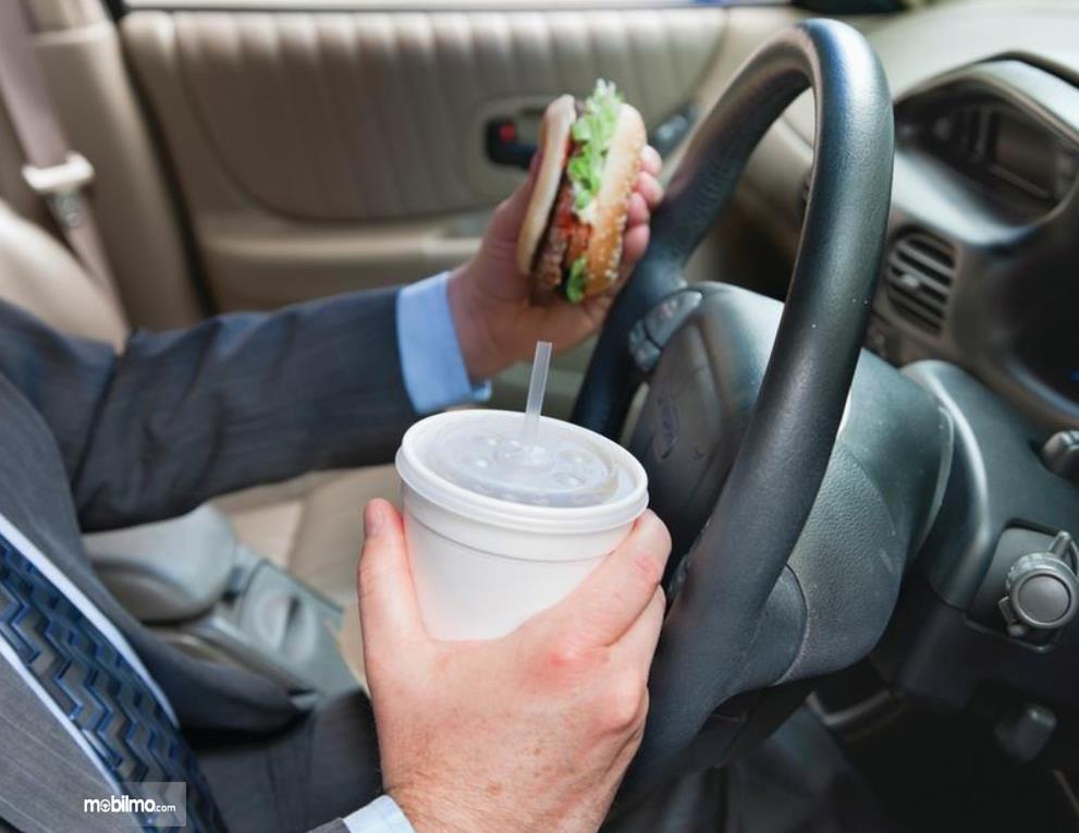 Gambar ini menunjukkan pengemudi memegang makanan dan minuman