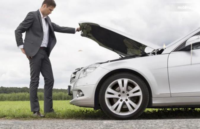 Gambar ini menunjukkan seorang pria membuka kap mesin mobil
