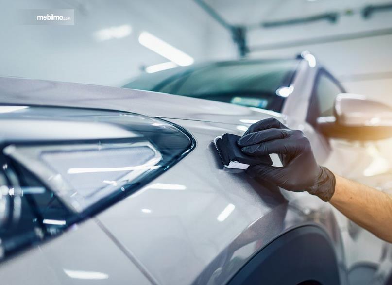 Gambar ini menunjukkan sebuah tangan menempelkan benda pada bodi mobil