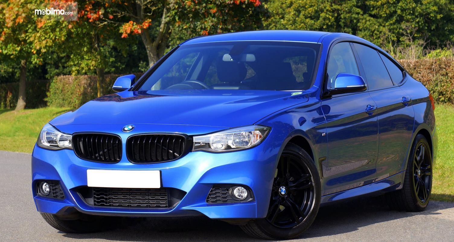 Gambar ini menunjukkan mobil warna biru tampak kinclong