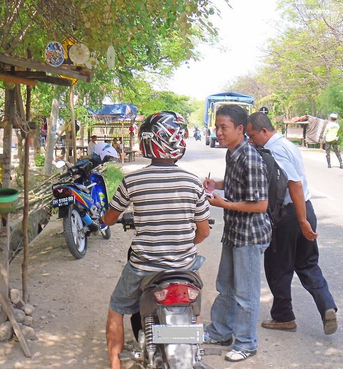 Gambar ini menunjukkan beberapa orang sedang bertanya pada pengendara sepeda motor