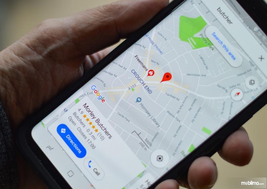 Gambar ini menunjukkan sebuah tangan memegang handphone tampilan GPS