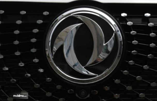Gambar ini menunjukkan emblem logo DFSK pada mobil warna krom
