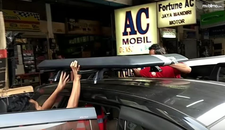 Gambar ini menunjukkan pemasangan roof rack pada mobil