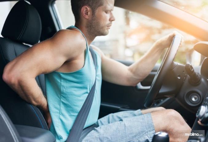 Gambar ini mneunjukkan pengemudi memegang pinggang