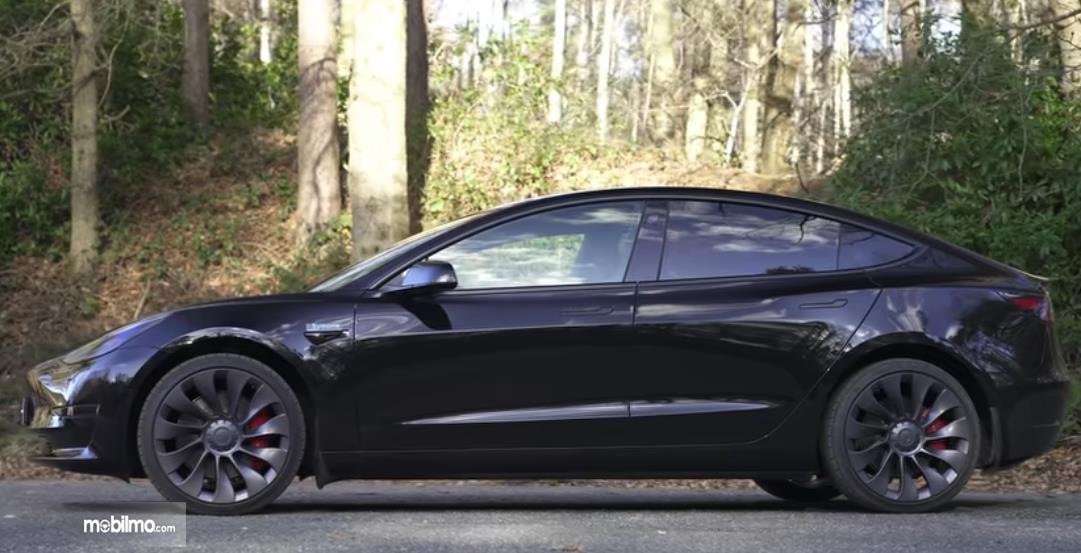 Gambar ini menunjukkan mobil listrik Tesla Model 3 tampak samping