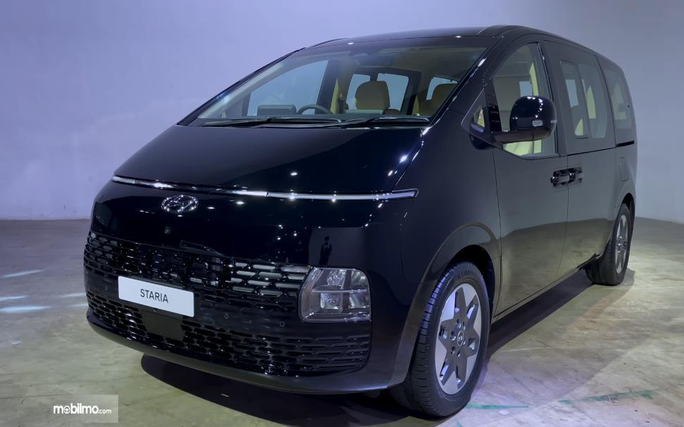 Gambar ini menunjukkan mobil Hyundai Staria tampak samping dan depan