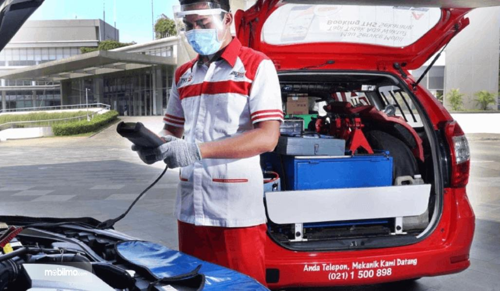 Gambar ini menunjukkan seorang mekanij mengecek mesin mobil