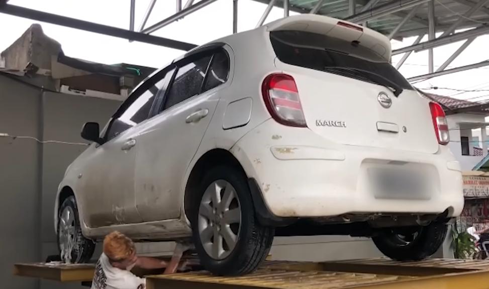 Gambar ini menunjukkan proses cuci mobil Nissan March