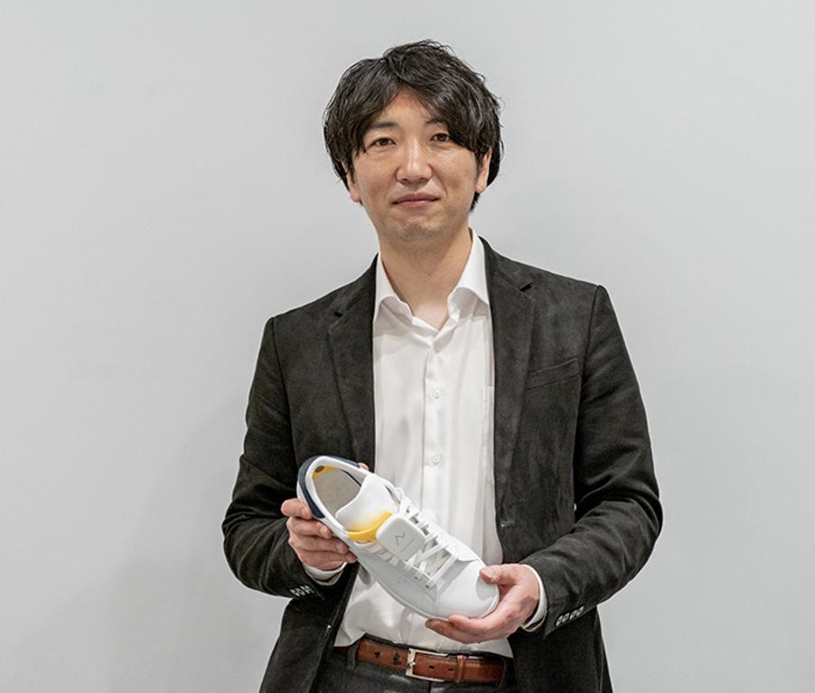 Gambar ini menunjukkan Wataru Chino memegang sepatu dengan sistem navigasi