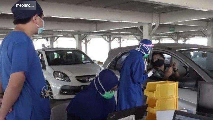 Gambar ini menunjukkan 2 orang berdiri dan berbicara dengan sopir di mobil