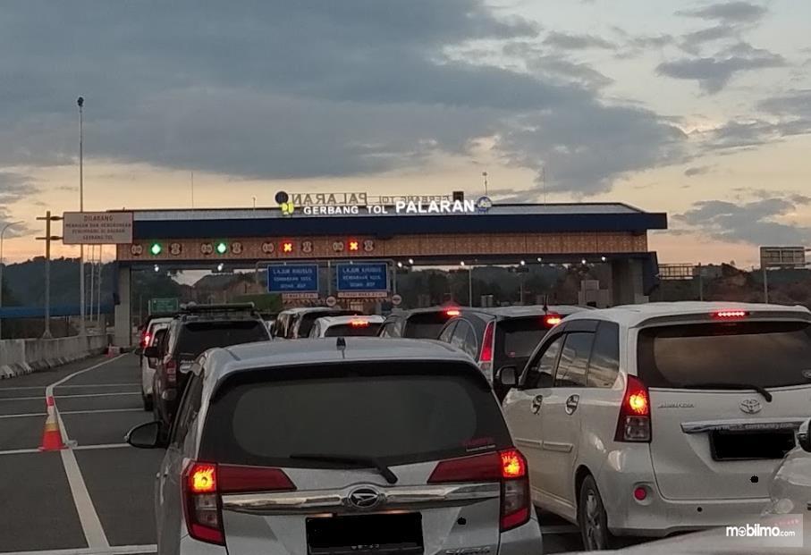Gambar ini menunjukkan banyak mobil di gerbang tol Palaran