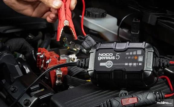 Gambar seorang yang sedang pakai charger untuk charge aki mobil