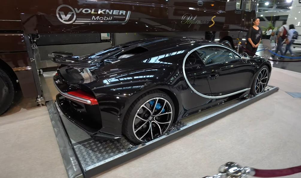 Gambar ini menunjukkan mobil Bugatti Chiron disamping motorhome Volkner