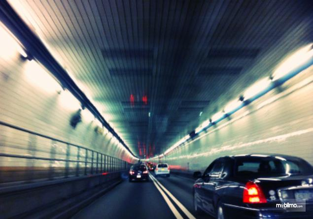 Gambar ini menunjukkan beberapa mobil melewati terowongan