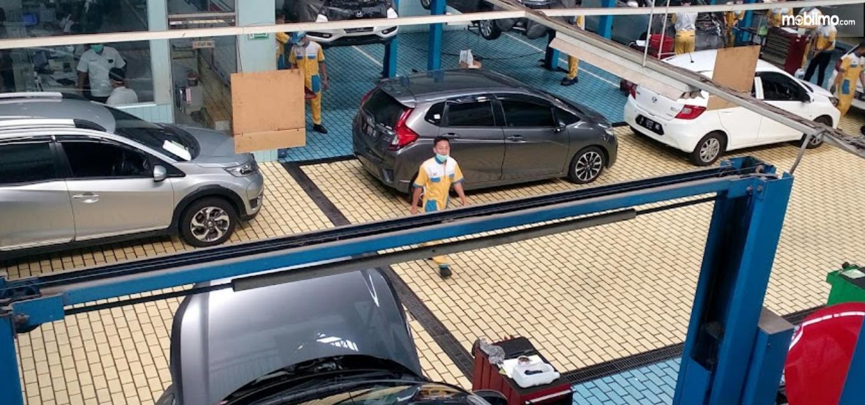 Gambar ini menunjukkan beberapa mobil di bengkel resmi Honda